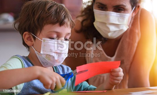 Caucasian Little boy at pre school classroom with his teacher, both wearing a protective face mask (picture taken in a real US classroom)