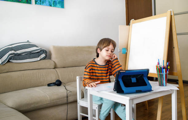 Little boy attending online classes from home. Tired and bored by home schooling. stock photo