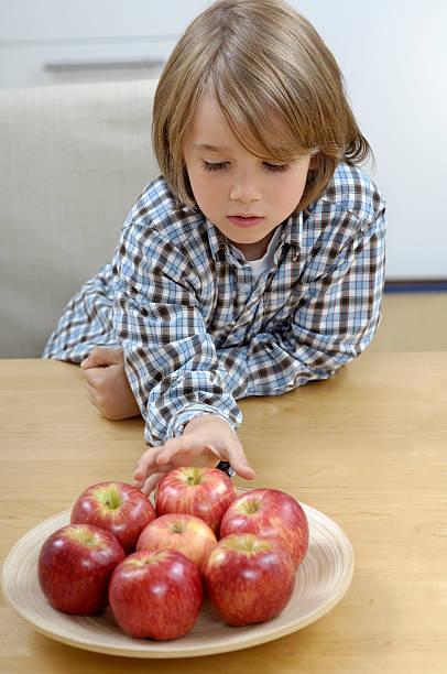 Kleine Junge hinter einem Teller mit roten Äpfeln – Foto