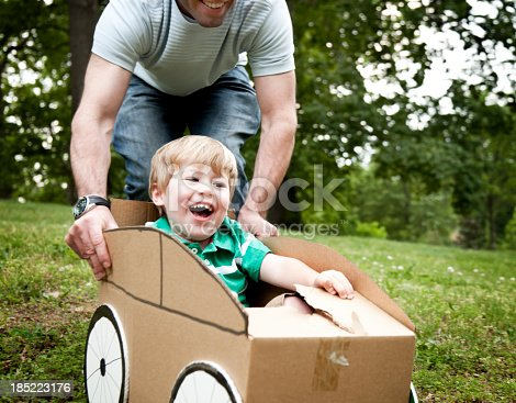 496487362 istock photo Little boy being pushed by his dad in a cardboard car 185223176