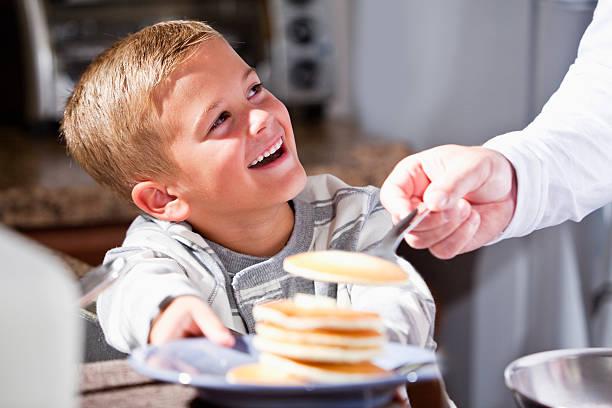 Kleine Junge serviert Pfannkuchen zum Frühstück – Foto