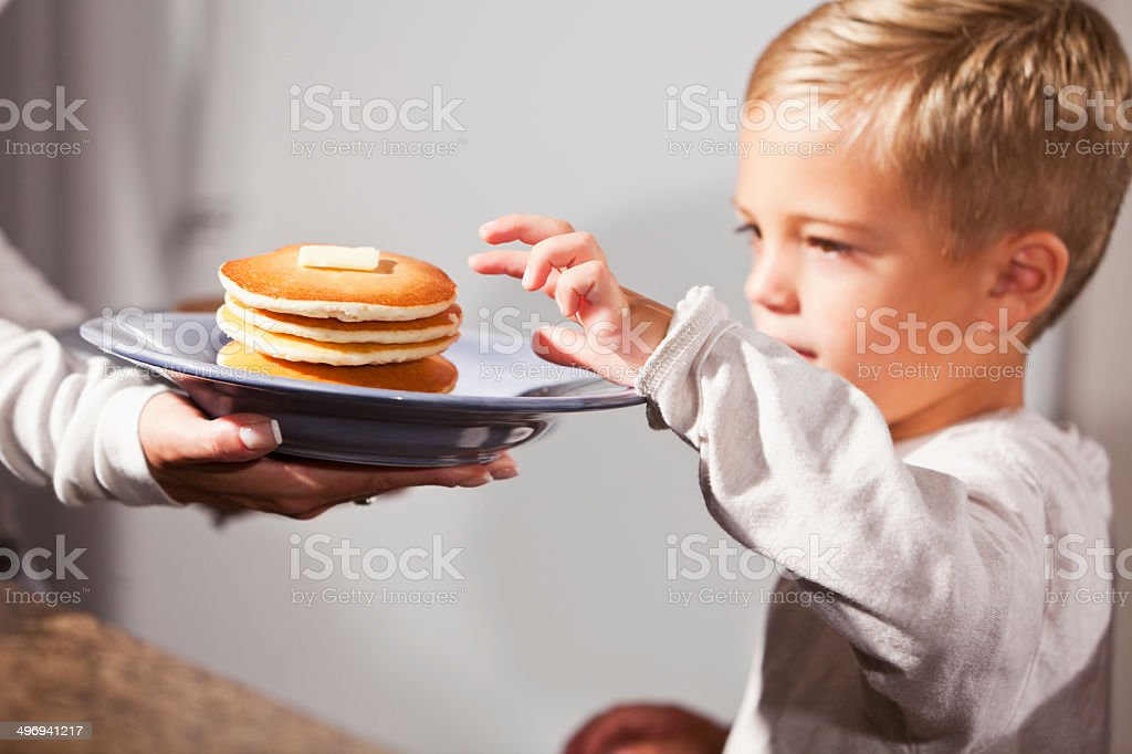Little boy being served pancakes for breakfast stock photo