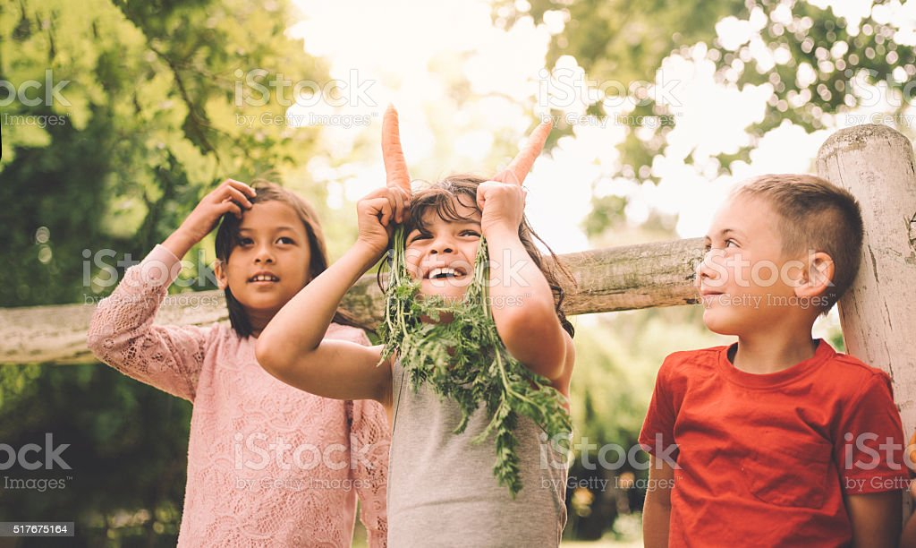 Little boy being silly with two carrots and his friends stock photo