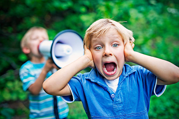 Little boy being yelled on by his brother Little boy covering his ears while his brother is yelling on him with megaphone. hands covering ears stock pictures, royalty-free photos & images