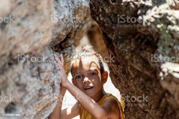 Photo of little boy between the rocks