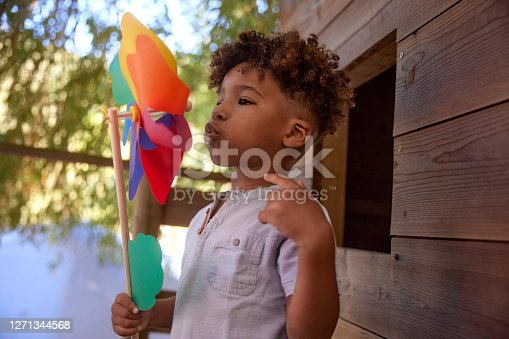 istock Little boy blowing colorful pinwheel on top of tree house 1271344568