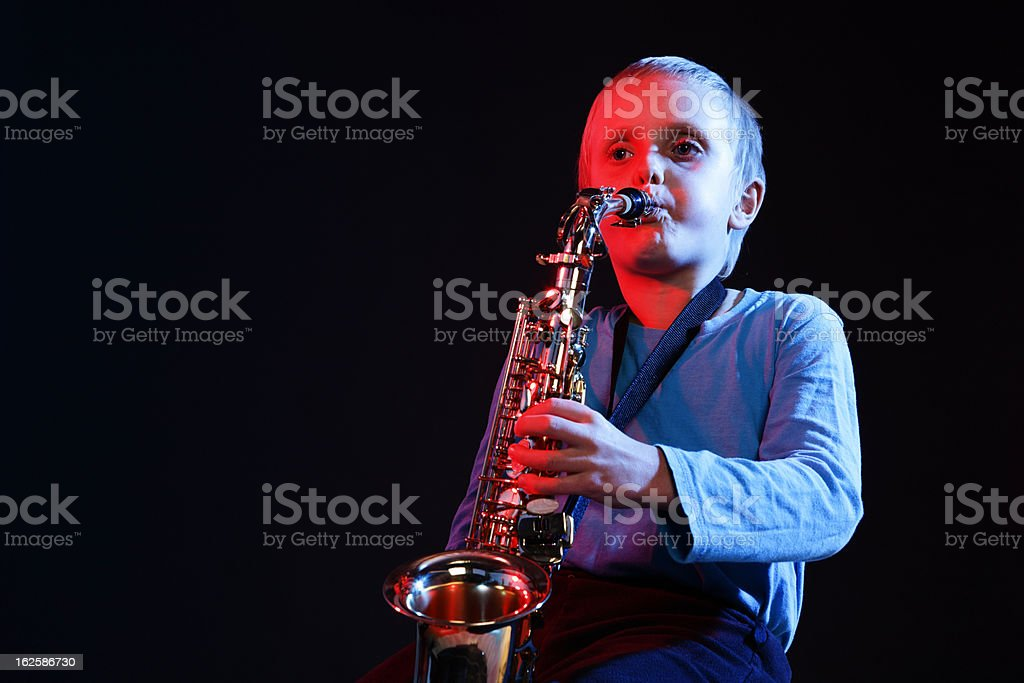 Little boy blue - young saxophonist plays against black background royalty-free stock photo