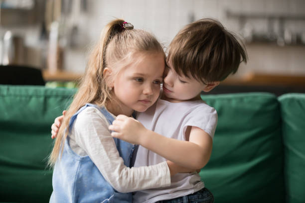 Little boy brother consoling and supporting upset girl embracing sister Little boy hugging consoling upset girl sitting on sofa, kid brother embracing sad sister apologizing or comforting, siblings friendship, preschool children good relationships and support concept sibling stock pictures, royalty-free photos & images