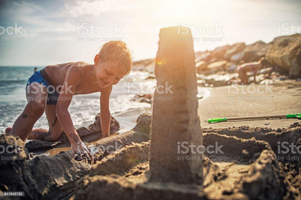 Little boy building sandcastle on italian beach stock photo