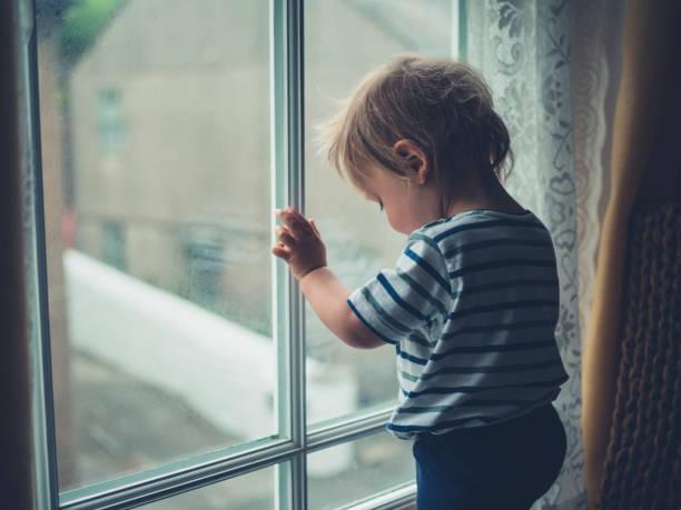 Little boy by window stock photo