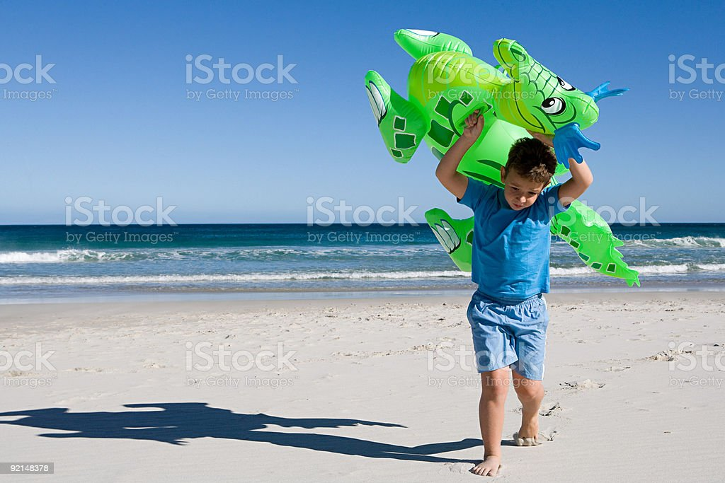 Little boy carrying inflatable dragon along beach stock photo