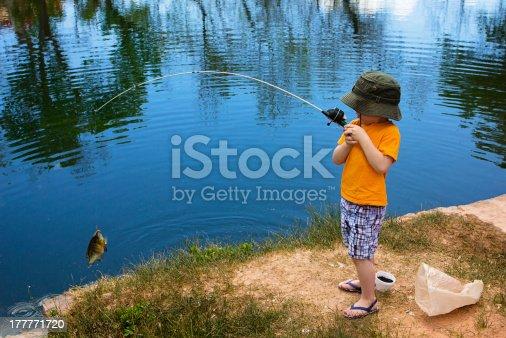 A cute little boy reeling in a big fish.