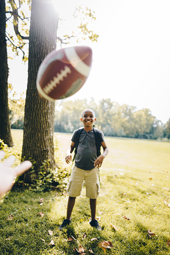 istock little boy catching the football at the park 867067368
