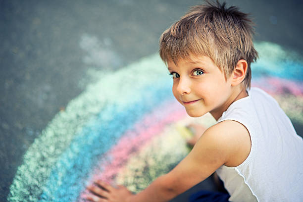 little boy chalking rainbow - chalk drawing stock photos and pictures