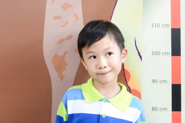Küçük çocuk onun yükseklik yükseklik ölçeği duvardaki kendisi tarafından ölçme ile okulda kontrol. Gülümseyen sevimli Asya çocuk onun yükseklik ölçer. Çocuk büyüyen kavramı stok fotoğrafı