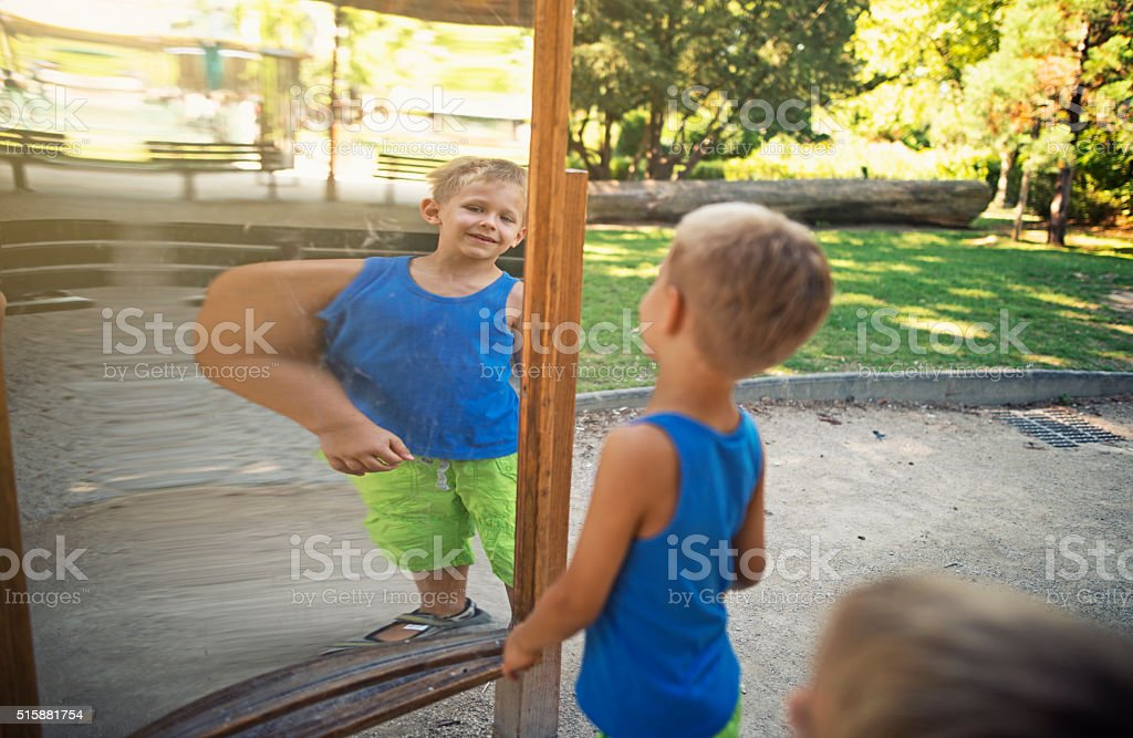 Little boy checking his muscles in funny distorting mirror stock photo