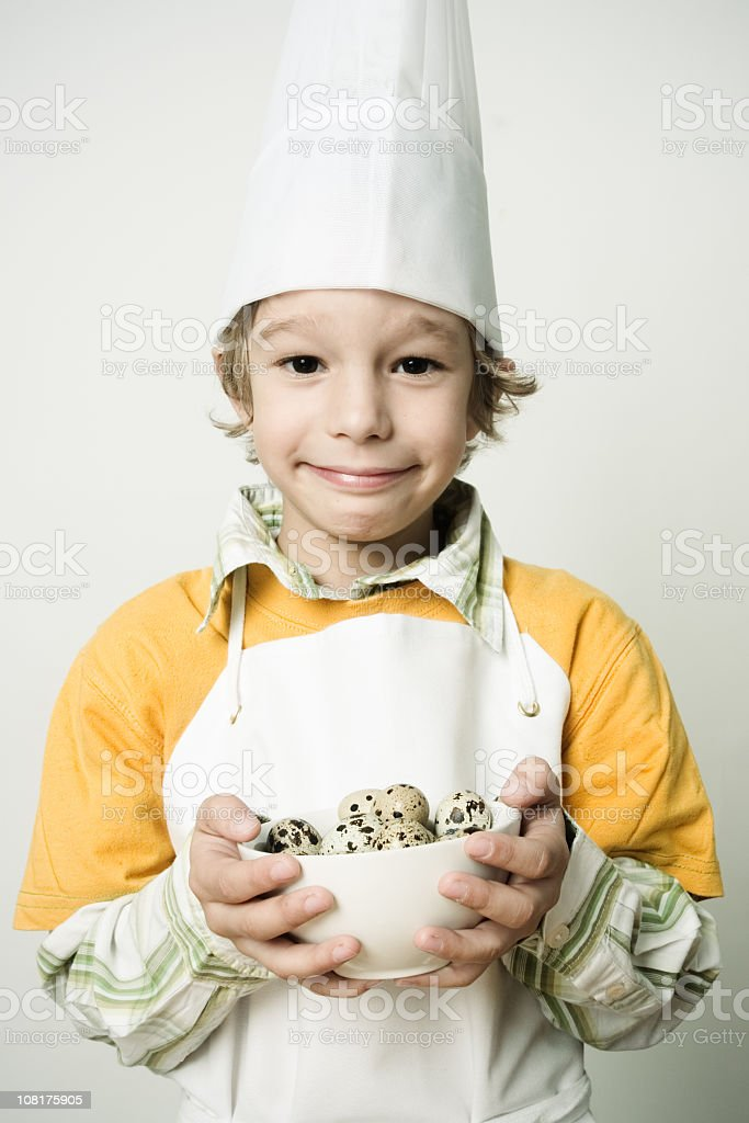 Little Boy Chef Holding Bowl of Eggs royalty-free stock photo