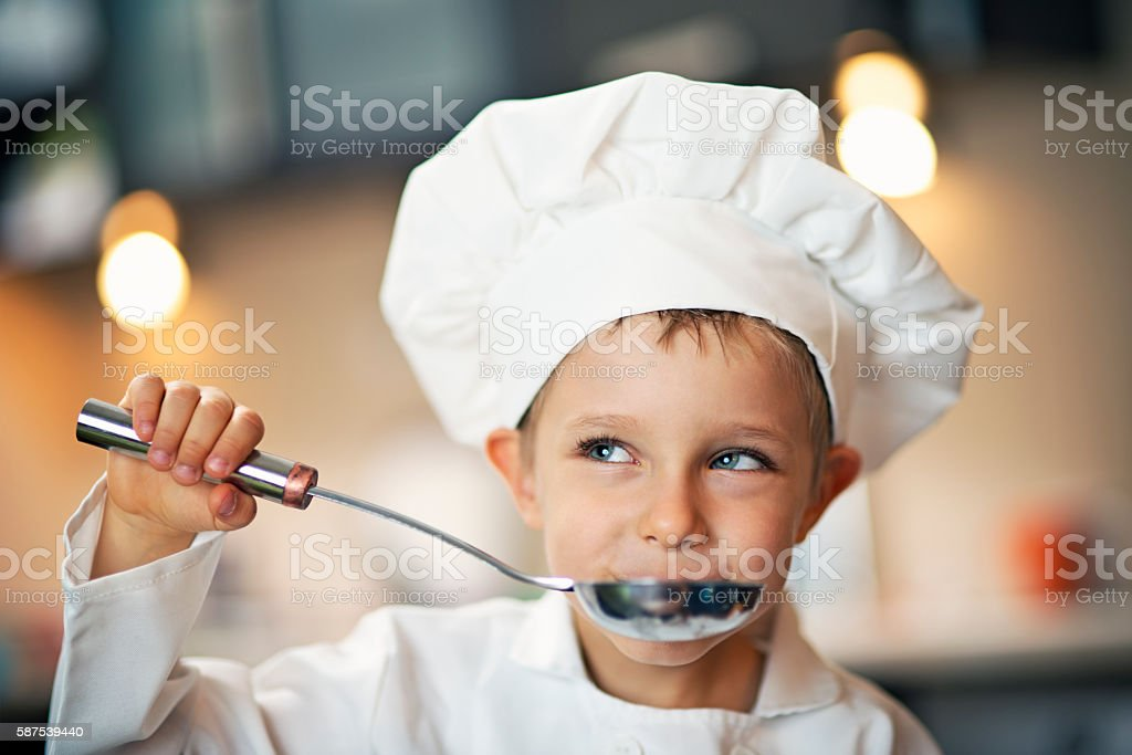 Little boy chef tasting soup. stock photo