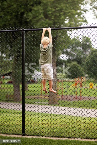 A Little boy child was trying to climb a tall chain link fence to secape to a playground, but is stuck hanging by his hands at the top.