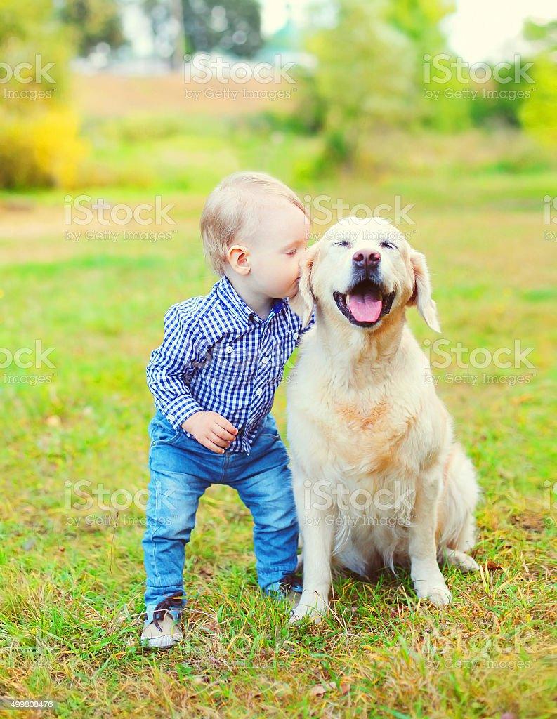 Little boy child kissing Golden Retriever dog on grass stock photo