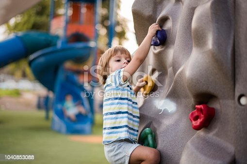 Small kid climbing on the wall and having fun on the playground.