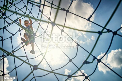 Portrait of little boy climbing in the playground. The boy aged 8 is smiling down at the camera from the climbing web. The sun and blue sky visible in the background. Nikon D850