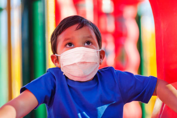 Little boy climbing into a kids playground while wearing a face mask to protect against viruses in public places. stock photo