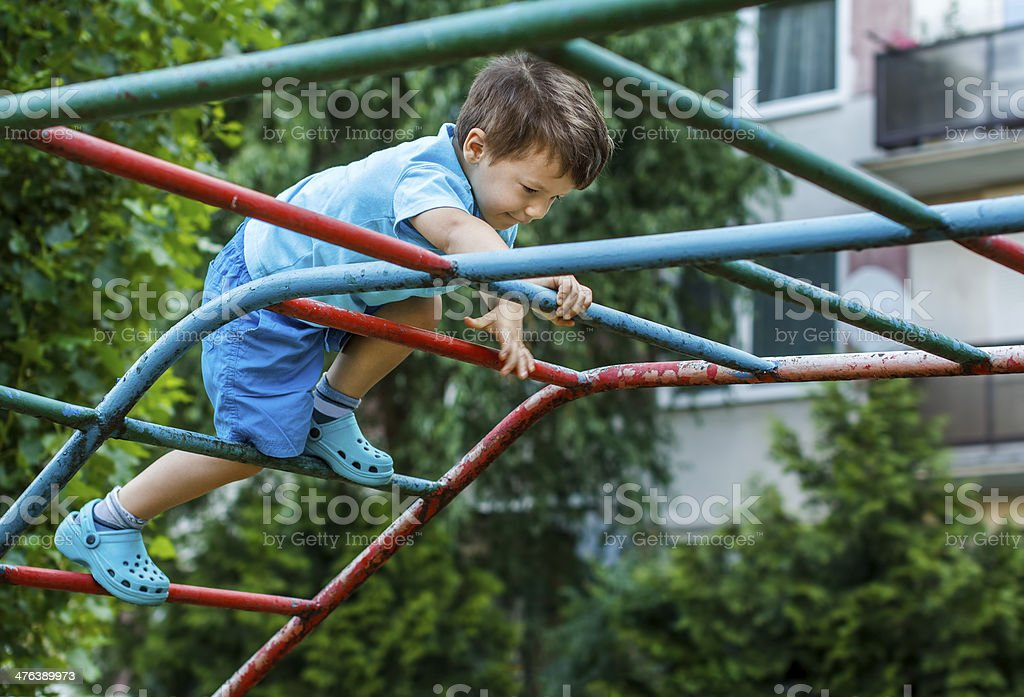 Little boy climbing on jungle gym without rope and helmet royalty-free stock photo