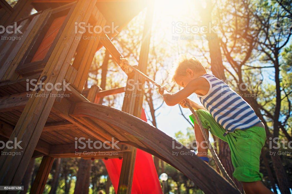 Kleiner Junge klettert auf dem Spielplatz - Lizenzfrei Kinderspielplatz Stock-Foto