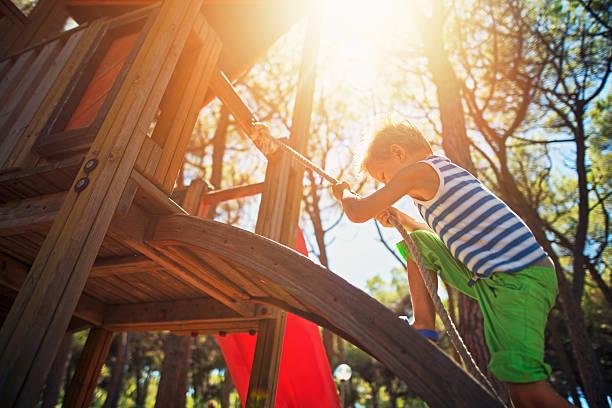 Little boy climbing on the playground stock photo