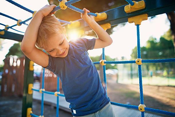 little boy climbing on the playground - kinderspielplatz stock-fotos und bilder
