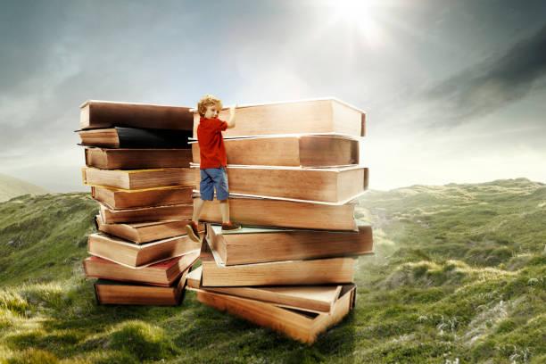 kleiner junge klettert auf den turm aus großen büchern - flyer inspiration stock-fotos und bilder