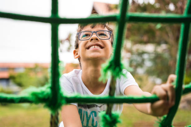little boy climbing rope frame - recess stock photos and pictures