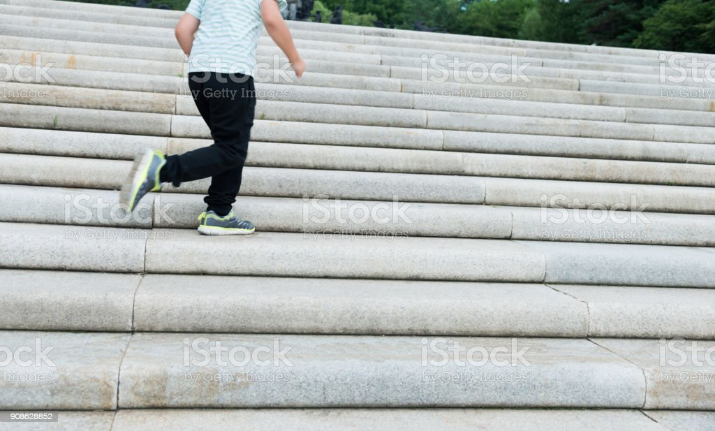 Little boy climbing stairs outdoors stock photo
