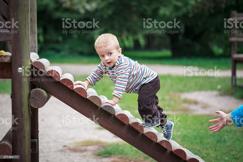 Little boy climbing wooden steps in a playground stock photo