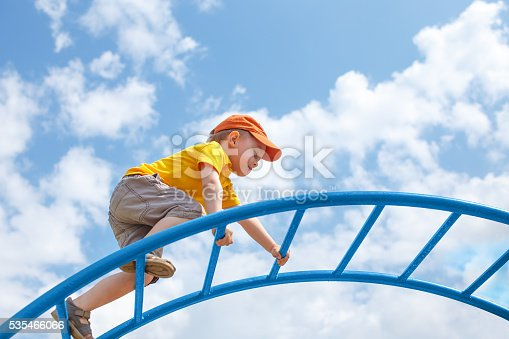 child climbs confidently up the ladder against the blue sky. copy space for your text