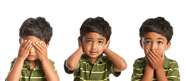 A little boy covering his eyes, ears and mouth stock photo