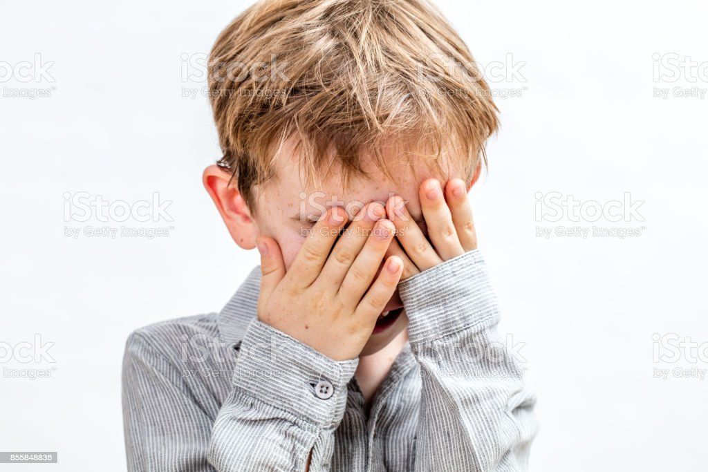 little boy covering his face for playing peekaboo or disappearing stock photo