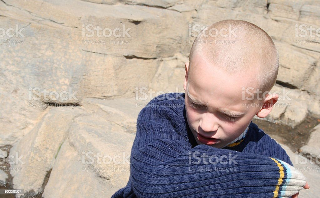 little boy covers mouth with sleeve as he sneezes coughs royalty-free stock photo