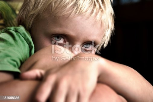 istock Little boy cowers away from camera 134958356