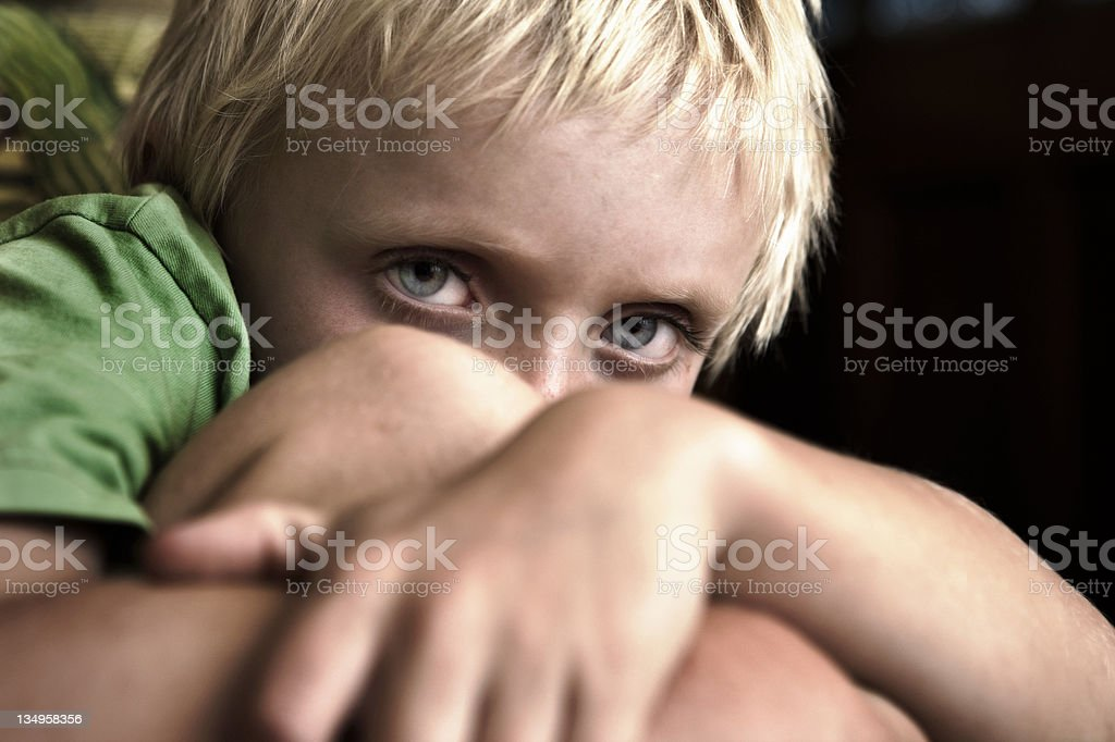 Little boy cowers away from camera stock photo