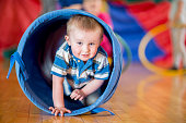 A little boy is crawling through a play tunnel at day care. He is smiling and looking at the camera.