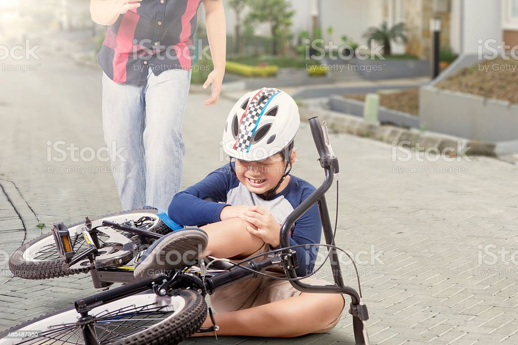 Little boy crying after falling from the bike stock photo