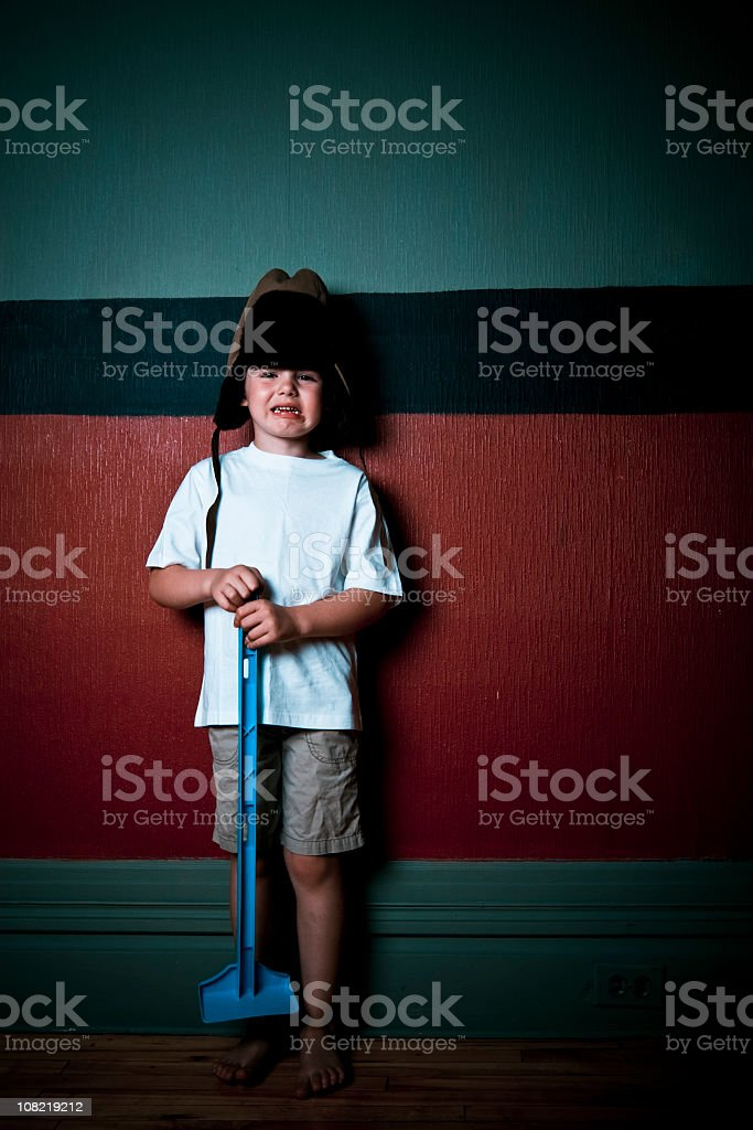 Little Boy Crying Holding Shovel and Wearing Aviator Hat royalty-free stock photo