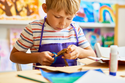Portrait of cute little boy cutting paper carefully in arts and crafts class of pre-school