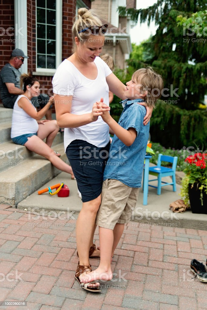 Little boy dancing on mother's feet in family gathering. stock photo