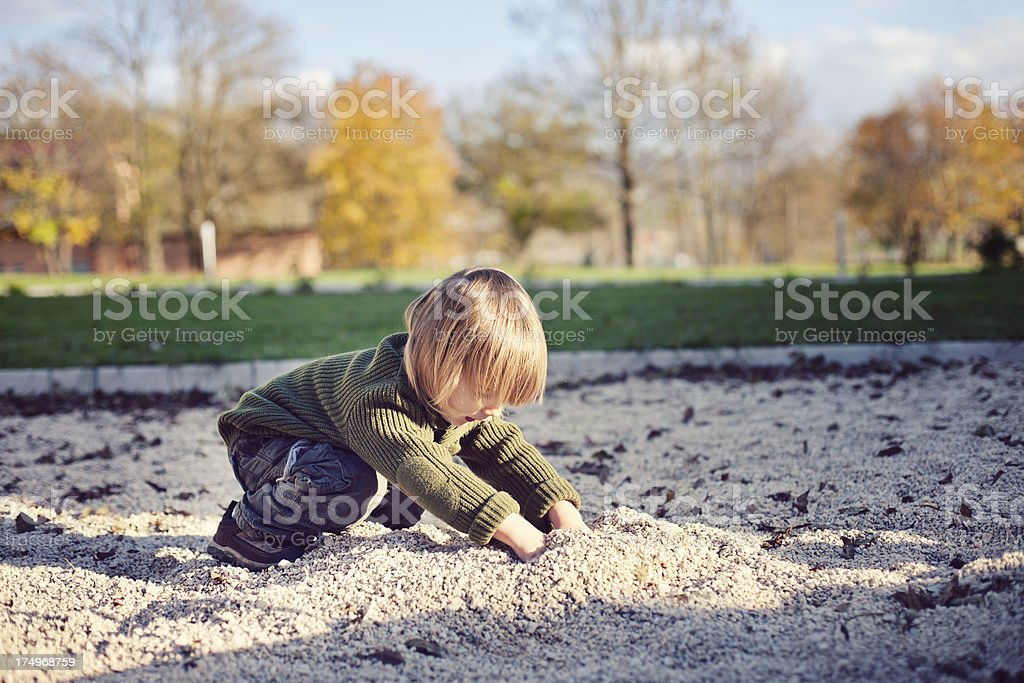 Little boy digging at the playground stock photo