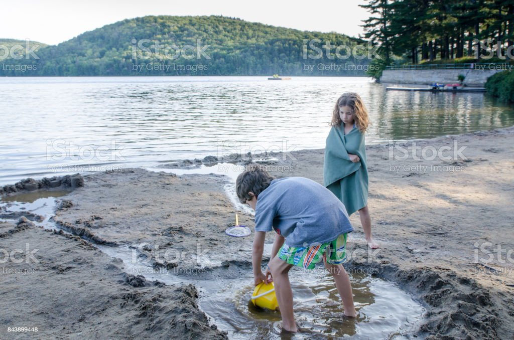 Little boy digging sand on beach besides the lake during summer vacations day stock photo