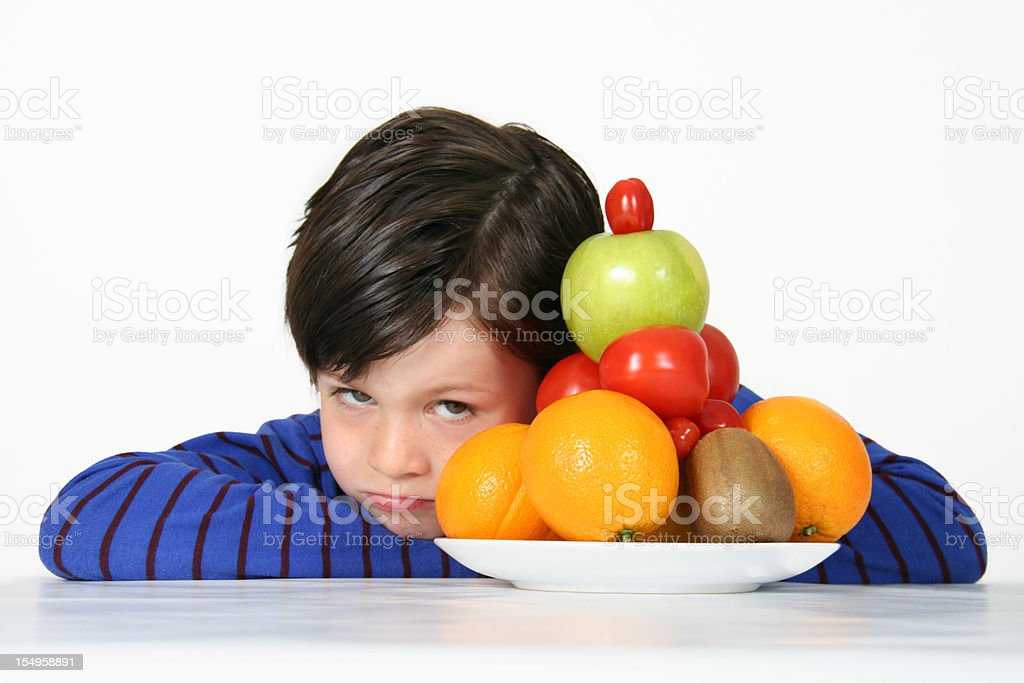little boy dislikes healthy food stock photo