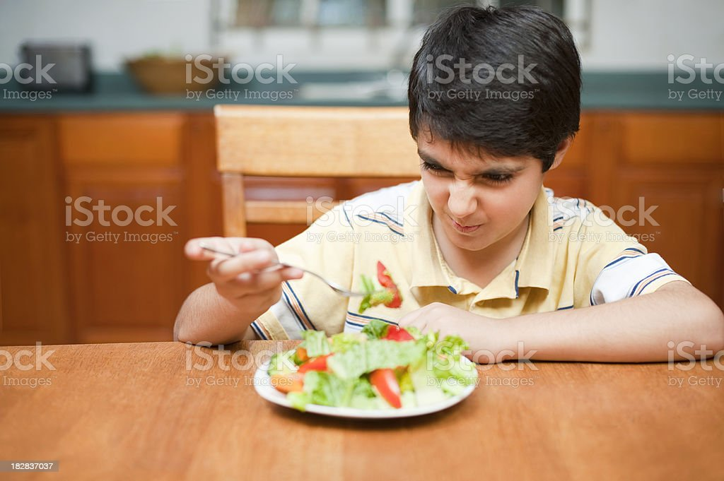 Little boy disliking his salad royalty-free stock photo